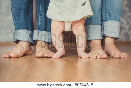 The feet of the Pope, mother and child, barefoot on the floor.