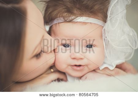 Young mother kissing her little newborn baby