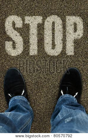 Man On A Tarmac Road With The Word Stop