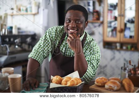 Happy young man selling buns in bakery shop