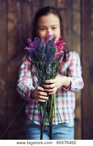 Little girl holding wildflowers in hands