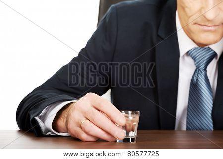 Overworked man drinking vodka in office.