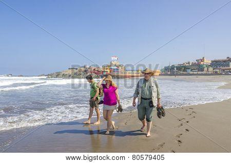 MOLLENDO, PERU, MAY 20, 2014: Tourist family walks on beach
