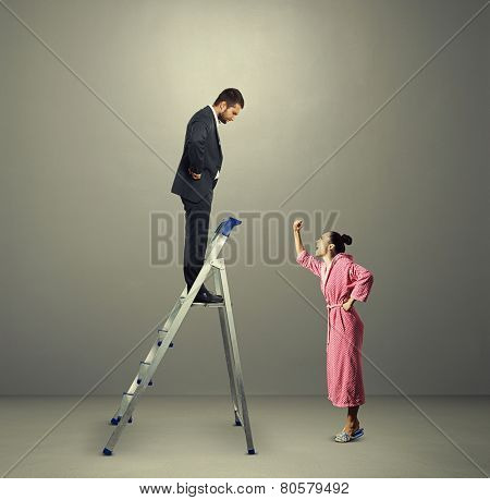 emotional woman screaming and showing her fist at displeased man on the stepladder over dark background