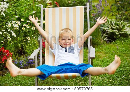 Happy child laying relaxed in deck chair in summer in a garden