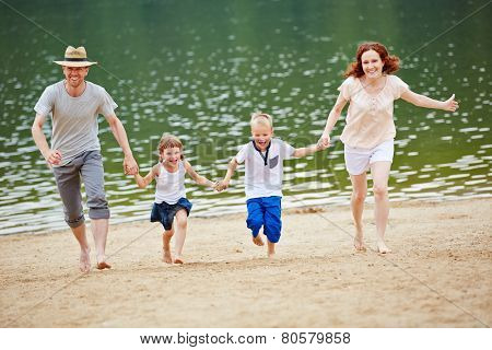 Happy family with two children outdoors running on beach on summer