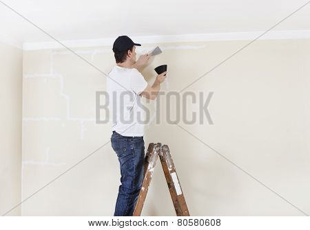 Man On Ladder Spackles Wall