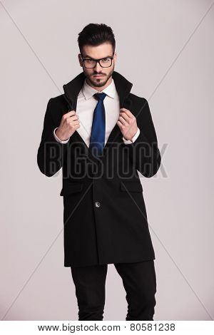 Handsome business man wearing a long black coat looking at the camera while fixing his collar.