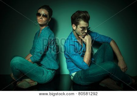 Man and fashion woman sitting back to back on studio background. she is looking at the camera while he is looking down thinking.