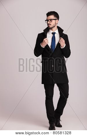 Full body picture of a elegant business man looking away from the camera while pulling his collar.