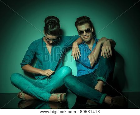 Fashion woman looking down and  arranging her shirt while her lover is sitting next to her looking at the camera.
