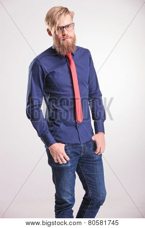 Young casual man holding both thumbs in his pockets while looking at the camera.