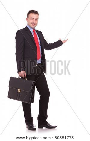 Side view picture of a handsome young business man holding a black brief case while presenting.