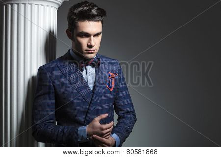 Picture of a young fashion man looking down while posing near white column.