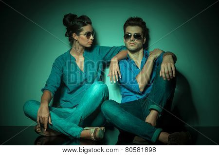 Full body picture of a fashion couple sitting on studio background, the woman si holding one arm on her lovers shoulder.
