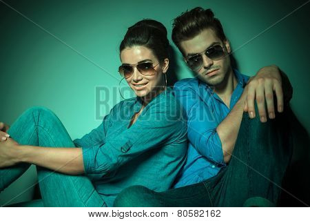 Fashion woman smiling and holding her leg with both hands while her boyfriend is leaning on her, both sitting.