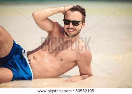 Smiling young man lying on the beach while fixing his hair. He is leaning on his elbow.
