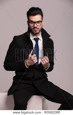 Young business man pulling his collar while sitting on a white modern chair.