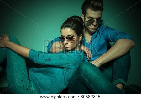 Side view of a beautiful fashion woman looking down while leaning on her lover, both sitting.