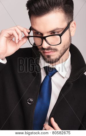 Close up picture of a handsome business man putting on his glasses while looking down.