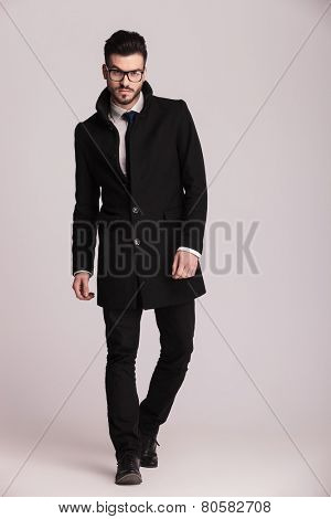 Handsome young business man wearing a long black coat walking towards the camera.