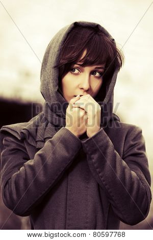 Sad young fashion woman in grey classic coat outdoor