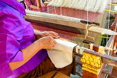 picture of loom  - Close up of old woman weaving silk on loom - JPG
