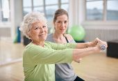 stock photo of dumbbell  - Senior woman exercising with fitness trainer at gym - JPG