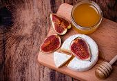 picture of meals wheels  - Camembert cheese with honey figs and honey dipper on a wooden board - JPG