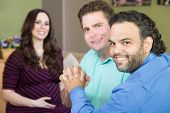 foto of vitro  - Handsome gay men holding hands with smiling surrogate mother - JPG