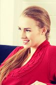 stock photo of pullovers  - Beautiful woman sitting on a couch and wearing red pullover - JPG