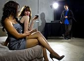 stock photo of seduce  - women seducing a man at a bar or nightclub - JPG