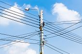 image of pole  - Electricity power wire and street lamp on concrete pole with blue sky - JPG