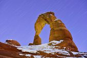 stock photo of arch  - Startrails and Delicate Arch in Arches National Park Utah in winter - JPG