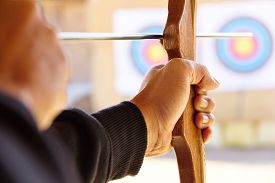 pic of bow arrow  - Archer holds his bow aiming at a target - JPG