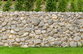picture of stockade  - background pattern gray color of modern style design decorative fence real stone wall surface with cement on green grass field - JPG