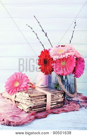 Beautiful bright gerberas in vase with old books on wooden background