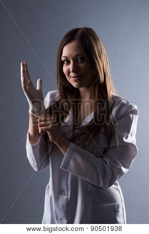 Female Beautiful Doctor Wear Rubber Medical Gloves In Contrasting Light