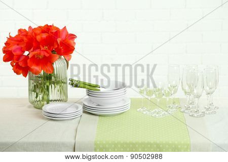 Table settings and tulip flowers in vase on table, on light background