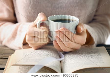 Woman holding cup of coffee and read the book, close up