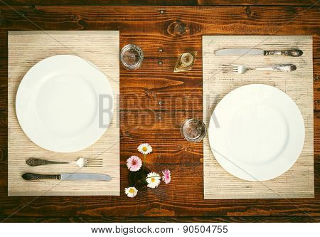 Table setting for two with empty plates - rustic wooden table