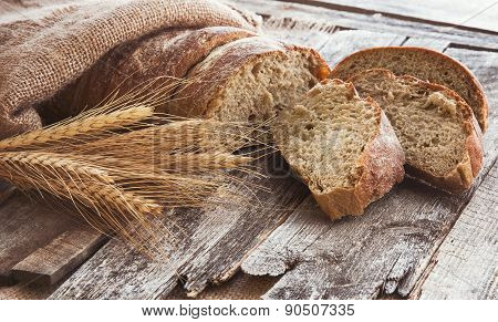 Fresh bread and wheat on the old wooden background. Toned