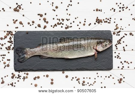 Trout fish on slate board with peppercorns