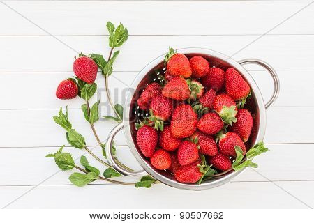 Fresh mint and strawberries in colander on white wooden table