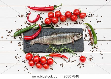 Trout Fish On Black Cutting Board With Cherry Tomatoes