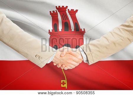 Businessmen Handshake With Flag On Background - Gibraltar