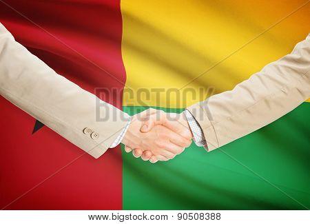 Businessmen Handshake With Flag On Background - Guinea-bissau