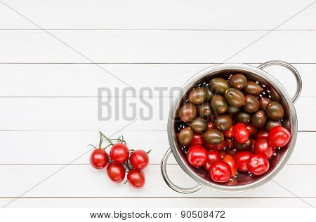Cherry tomatoes in colander on white wooden table. Top view