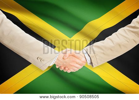 Businessmen Handshake With Flag On Background - Jamaica