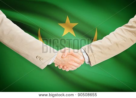 Businessmen Handshake With Flag On Background - Mauritania